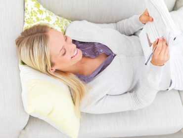 Smiling young businesswoman lying on sofa and writing documents
