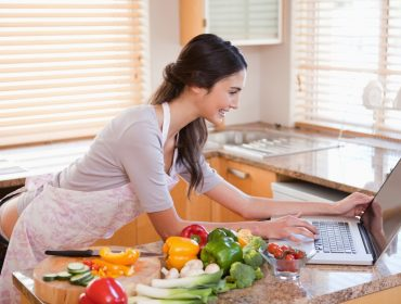 Woman looking for a recipe on the internet in her kitchen